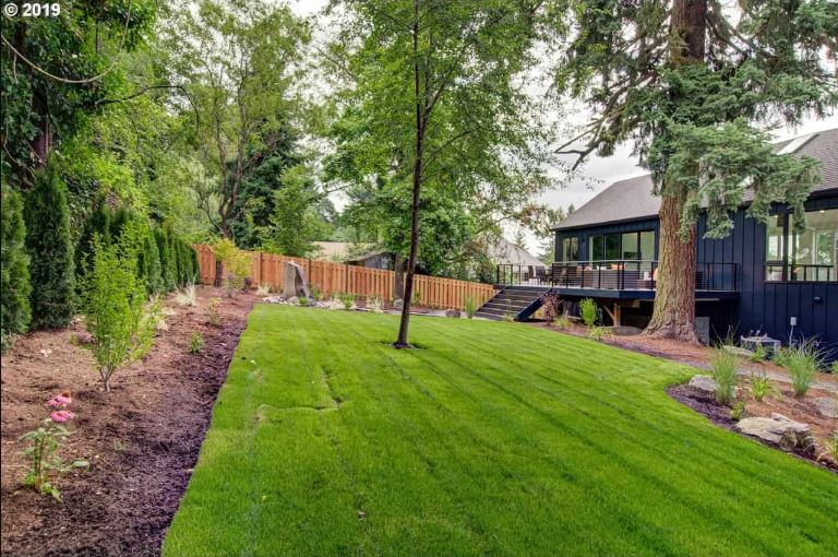 This simple green lawn at the backyard is surrounded by evenly spaced plants with shrubs and herbs in the mix. At the far end you can see the wooden fencing that surrounds the property and on the adjacent side to it is a row of tall shrubs that provide ample privacy.