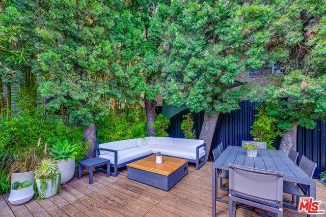 This backyard has a wooden plank flooring that complements the blue-gray wooden outdoor furniture of the outdoor dining area and the sitting area beside it that has an L-shaped wooden bench with white cushions that stand out against the background of green shrubs and tall trees.
