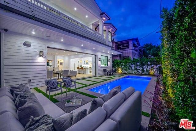 This backyard has a comfortable L-shaped gray sectional sofa at the sitting area beside the brilliant blue swimming pool. This wonderful area is surrounded by high white walls adorned with creeping plants and tall shrubs lit with yellow spotlights.