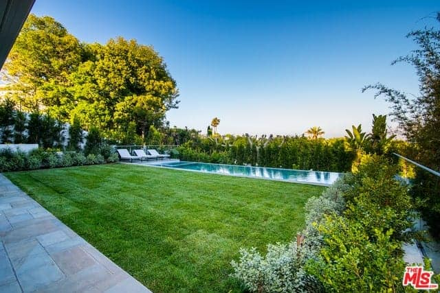 This is an amazing piece of backyard with a Farmhouse-style landscaping. The property is surrounded by tall shrubs that provide fencing and privacy for those enjoying the lawn of well-maintained grass and the pool on the far side with white lawn chairs.