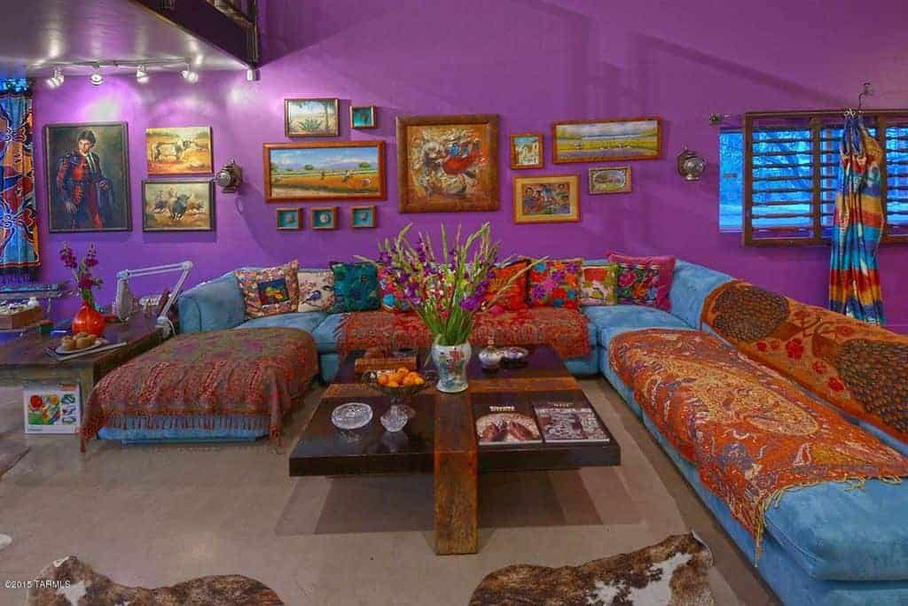 Purple living room designed with gallery frames mounted above the blue velvet sofa. There's a dark wood coffee table in the middle topped with bowls and flower vase.