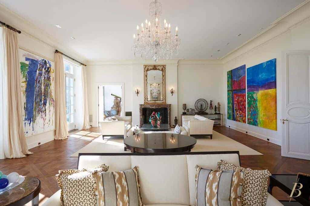 A fancy crystal chandelier illuminates this living room featuring multiple seats and colorful abstract paintings mounted on the white walls. It includes a fireplace and rectangular mirror flanked by candle sconces.