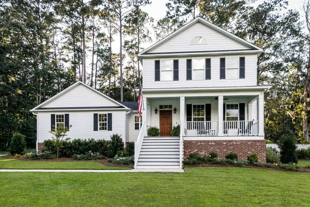 The white exterior walls of this house is paired with a gorgeous lush green landscape filled with tall trees in the background that are even taller than the house, and shrubberies that line the front of the house following the lay of the walls.