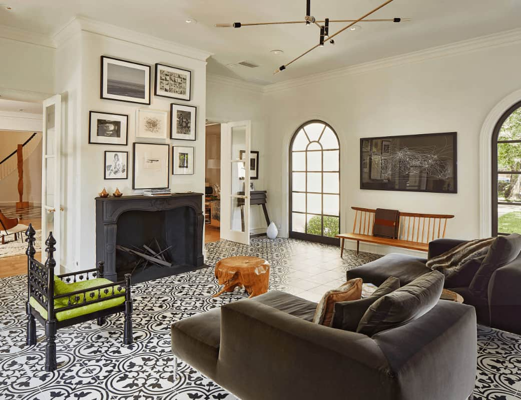 Airy living room with decorative tile flooring and gallery wall art mounted above the black fireplace. It includes velvet chaise lounges and a green cushioned chair paired with a stump coffee table.