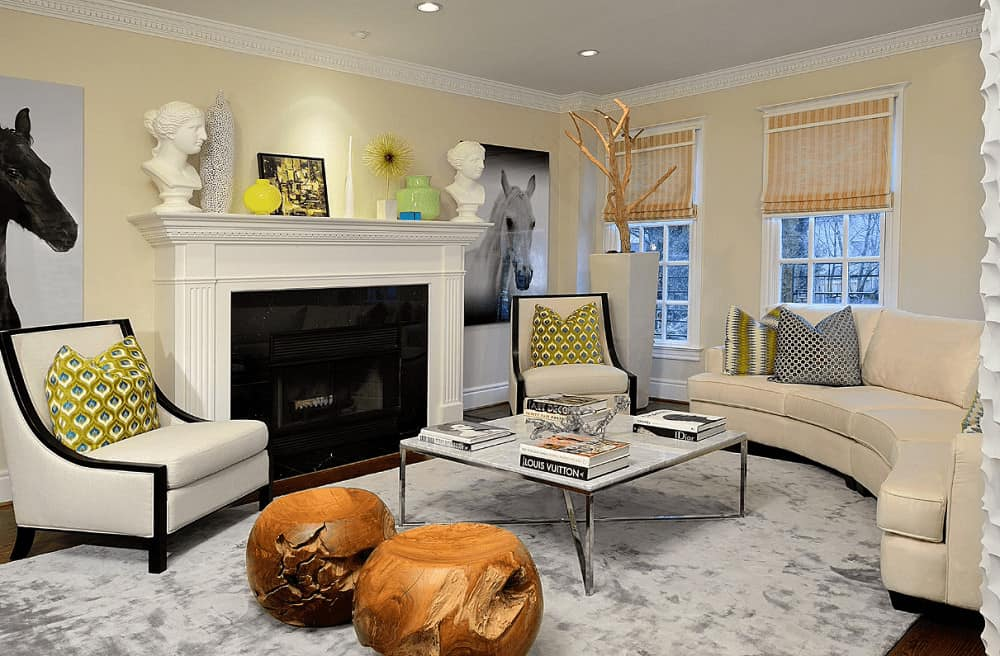 Beige living room decorated with horse artworks and bust sculptures that sit on the white fireplace. It has cozy seats and a metal coffee table with a pair of wooden ottomans on the side.