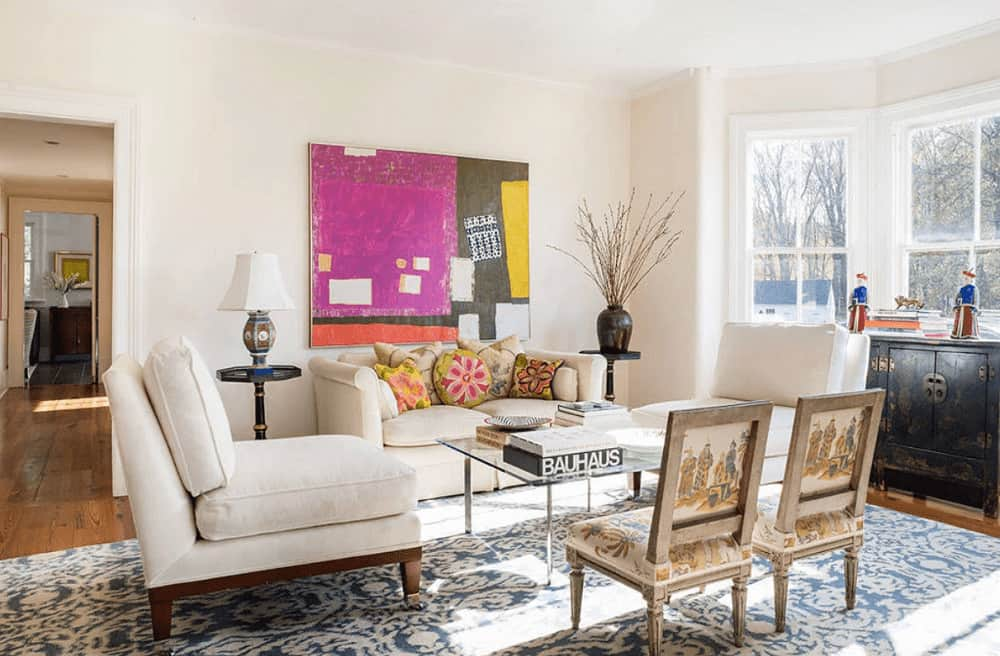 A colorful artwork adds a nice accent in this white living room boasting cozy seats and a glass top coffee table over a blue patterned rug.