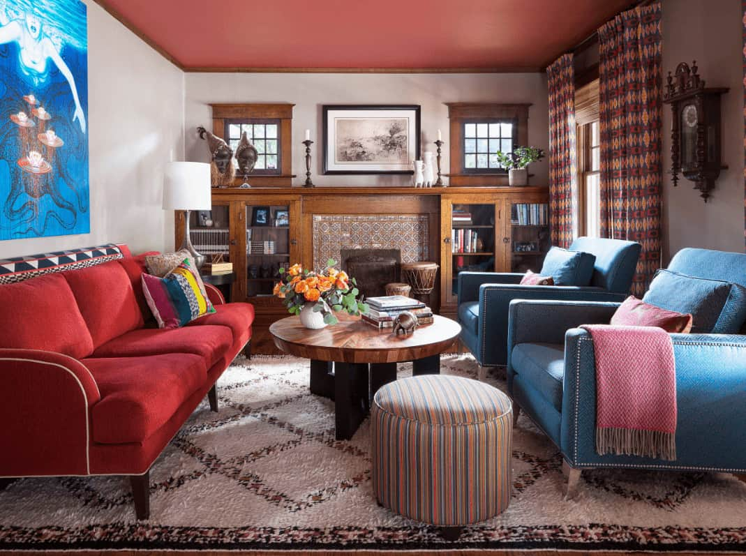 The eclectic living room offers red sectional and blue armchairs with a round coffee table and striped ottoman in the middle. It includes lovely artworks and a fireplace framed with decorative surround tiles.