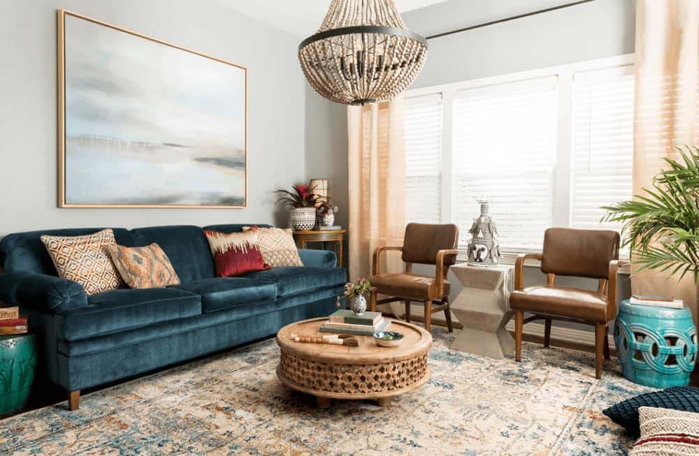 A wooden framed wall art hangs above the velvet sectional that's accompanied by cushioned chairs and round coffee table on a vintage area rug lighted by a large chandelier.
