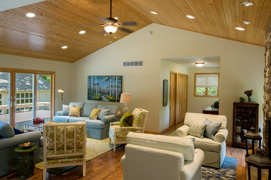 This living room offers multiple seating areas and a gorgeous painting mounted above the gray sectional sofa. It is illuminated by a flush light and recessed ceiling lights fitted on the cathedral ceiling.