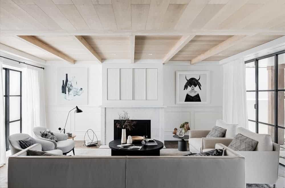 White living room decorated with interesting wall arts mounted above the white wainscoting. It has a fireplace and gray seats paired with a black coffee table.