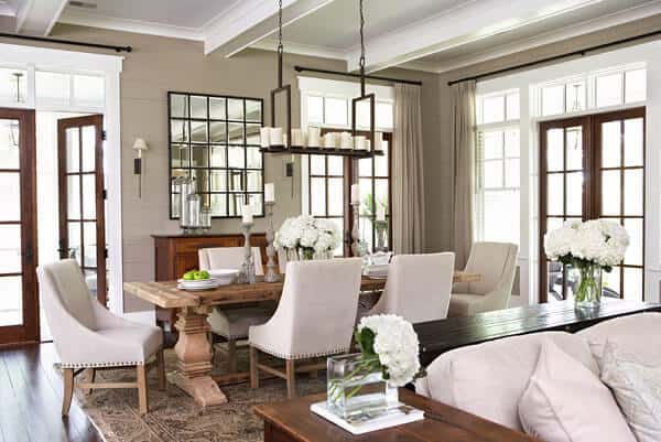 The white coffered ceiling of this dining area beside the living room supports a decorative lighting over the wooden dining table. This looks like a tray filled with candles that matches the candelabras on the dining table that is surrounded with white cushioned chairs.