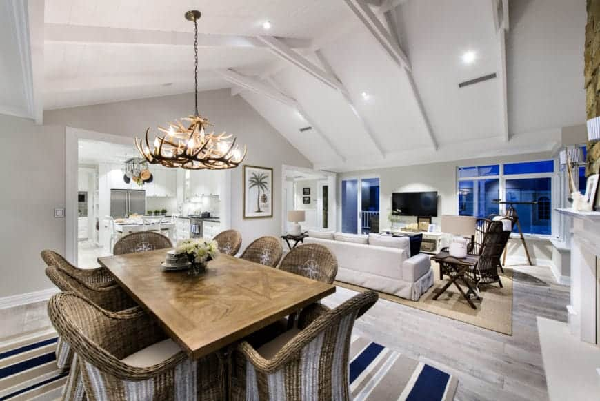 This great room that houses both the dining area and the living room area has a high white cathedral ceiling with exposed beams. It hangs a majestic antler chandelier over the wooden dining table that is partnered with woven wicker chairs.