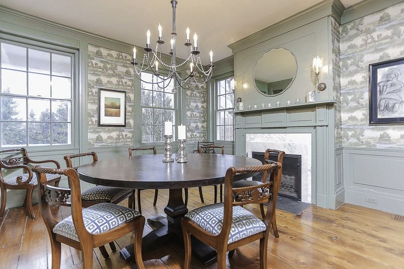 This elegance of the wrought iron chandelier is augmented by the green patterns of the wallpaper. These complete with the windows for dominance over the walls that has a fireplace that warms those dining on the wooden dining table.
