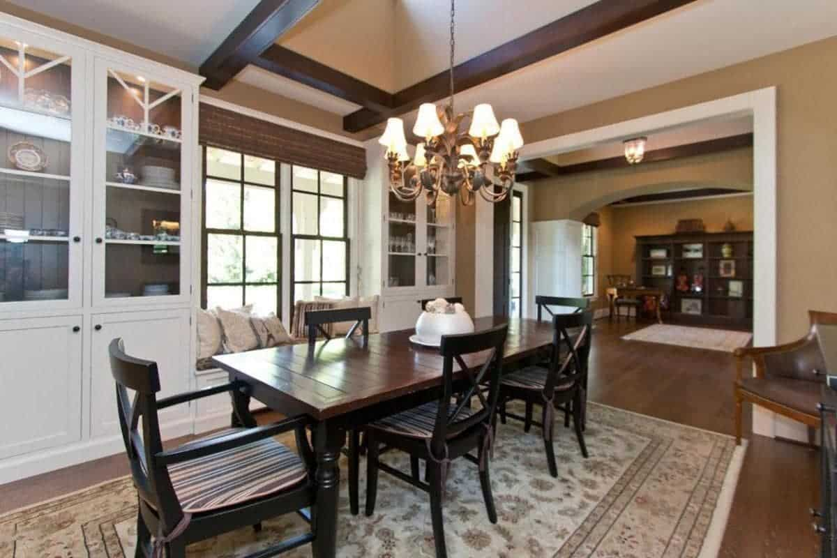 The beige ceiling has wooden exposed beams that have a dark brown hue matching with the hues of the Farmhouse-style wooden dining set over the beige patterned area rug of the dark hardwood flooring. These are all augmented by the yellow lights of the chandelier.