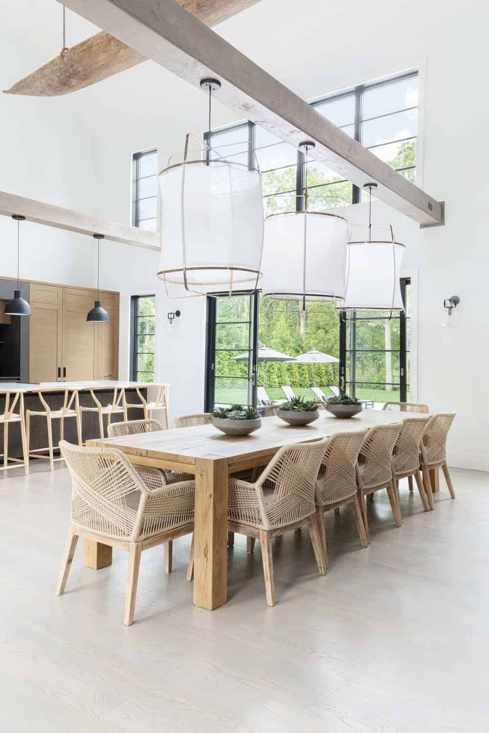 The high ceiling is paired with tall white walls with tall windows that bring in an abundance of natural lighting that complements the wooden dining table paired with rustic woven wicker armchairs. This is topped with a large floating beam supporting hooded pendant lights.