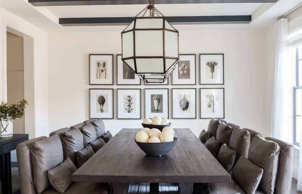 This is a Farmhouse-style dining room with comfortable dining chairs that have brown leather cushions and pillows that makes them look like living room chairs. They blend with the dark wooden dining table that is topped with pendant lights hooded with frosted glass.