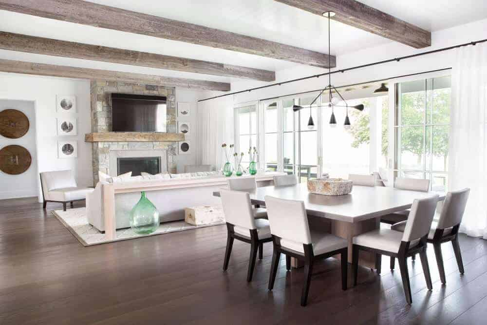 There is an ample supply of natural lighting cascading into this dining area beside the living room. This brightens up the dark hardwood flooring and the dark wooden legs of the white cushioned chairs surrounding the rectangular wooden dining table.