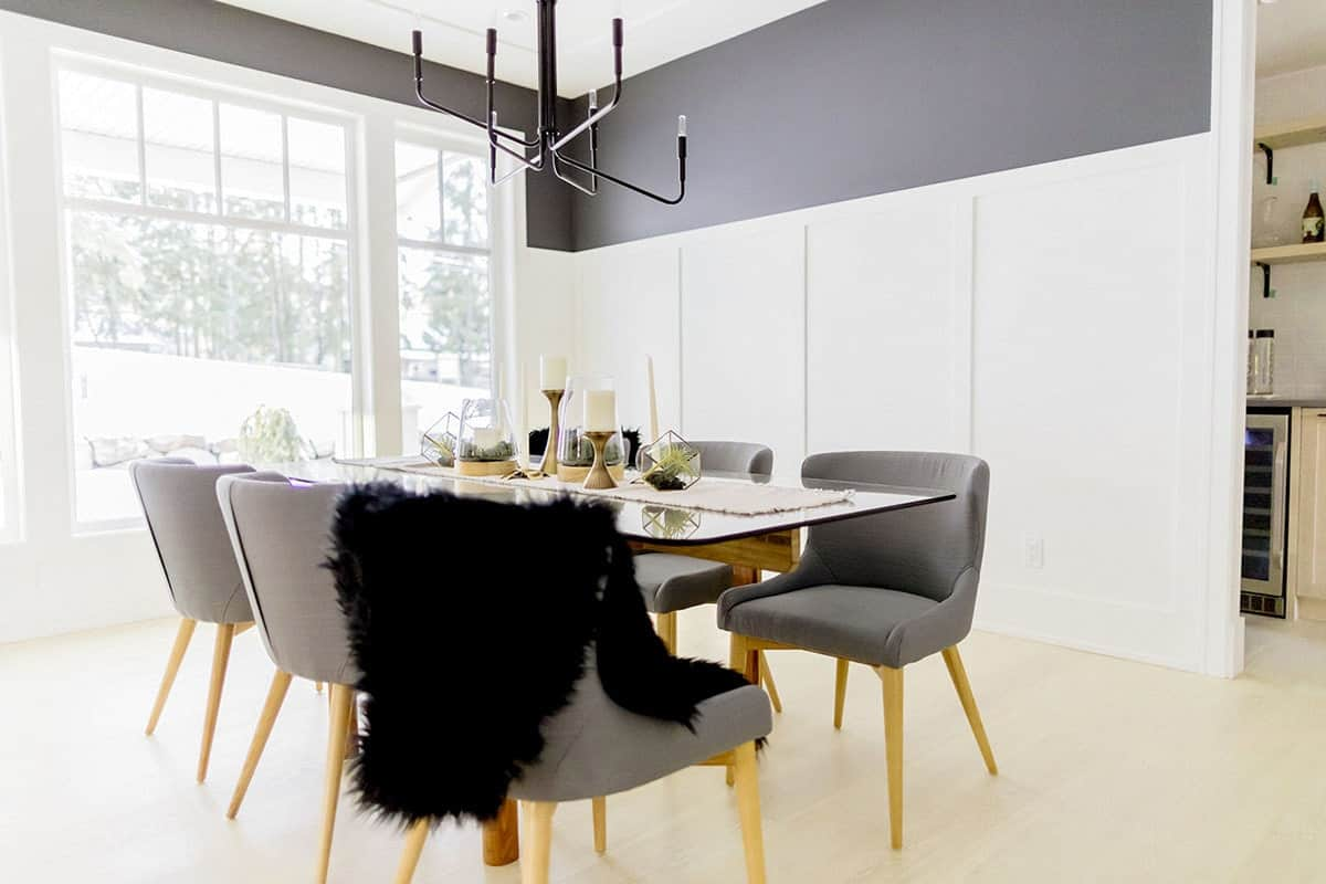 The walls have a white wooden finish like a tall wainscoting and then contrasted by the upper walls that have a dark gray hue. This complements the gray cushioned dining chairs of the glass-top dining table that is illuminated by the large white window.