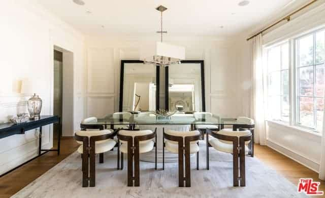 The white walls and ceiling of this Farmhouse-style dining room are further brightened by the ample natural lighting coming from the large curtained window by the head of the rectangular glass-top dining table paired with modern chairs.