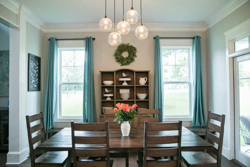 There are four beautiful pendant lights hanging from the ceiling that have spherical glass hoods. This sets a simple yet classy adornment to the dark wooden dining table and its simple dining chairs. This setup matches with the dining room cabinet flanked with green curtained windows.