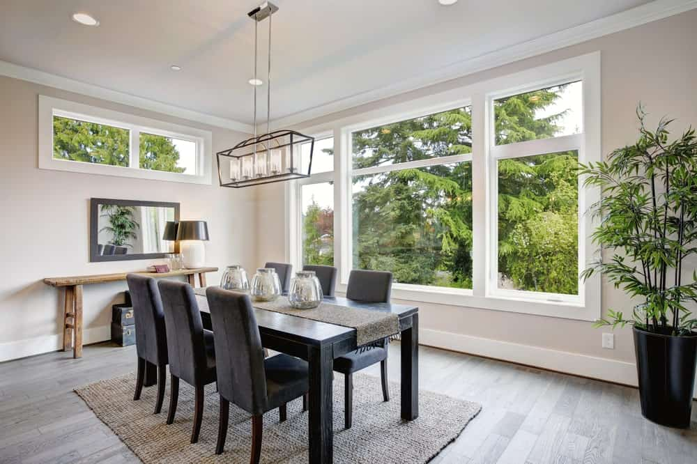 The lush green scenery outside the windows serve as a great bright background for the dark wooden rectangular dining table and its matching black velvet cushioned Parson's chairs over a rustic woven area rug matching with the table runner.
