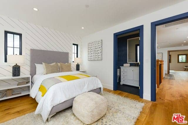 This is a bright and spacious Farmhouse-style bedroom that has a cathedral with a single wooden exposed beam that matches with the hardwood flooring and the frames of the surrounding windows that brighten up the white walls and gray traditional bed.
