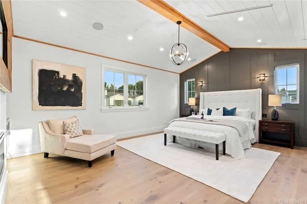 This spacious bedroom has a white cathedral ceiling that has a single exposed wooden beam running the middle supporting the spherical decorative pendant light. The white tufted headboard of the traditional bed stands out against the dark gray wall with a Farmhouse-style finish to it.
