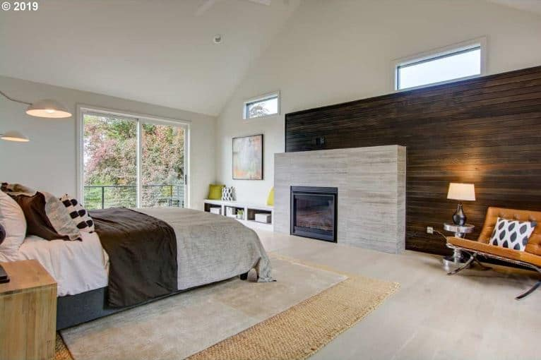 The light hardwood flooring of this elegant Farmhouse-style bedroom is topped with a rustic woven area rug paired with a gray area rug on top of it. This is a perfect match for the concrete slab that houses the modern fireplace by the foot of the bed. This concrete slab is adorned with a large wooden wall with a plank finish.