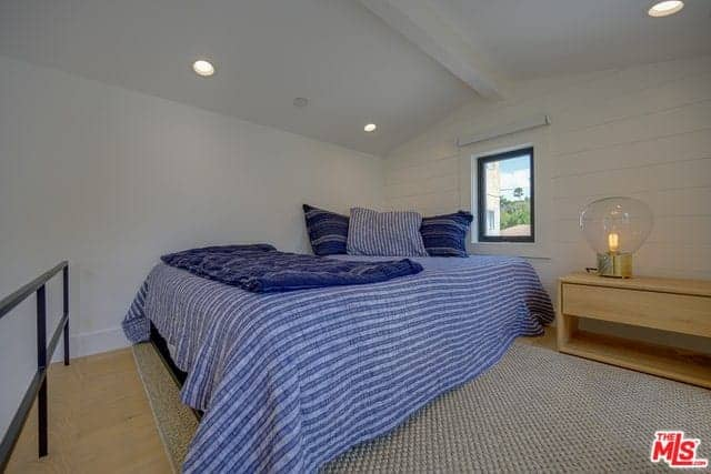 This is a comfortable bedroom on a wooden loft that has a low white cathedral ceiling with an exposed wooden beam in the middle and recessed lights on the side. The bed has a blue striped sheet that makes it stand out against the white walls that has a plank finish.