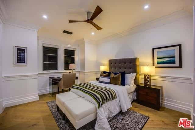 This is a simple bedroom with white walls, white ceiling and white wainscoting. The ceiling is adorned with a dark brown ceiling fan. This matches with the dark brown wooden bedside drawers that adorn the white walls and hardwood flooring.