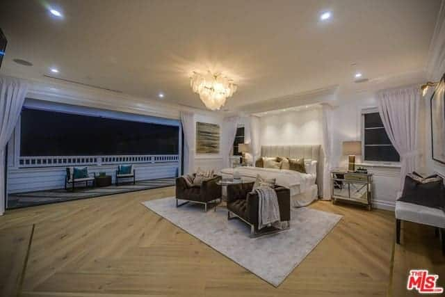This is a large master bedroom that has a Farmhouse-style wide hardwood flooring and a large wall that opens up to a balcony. The wide beige ceiling has recessed lights on the sides and the a large decorative lighting in the middle over the sitting area by the foot of the bed.