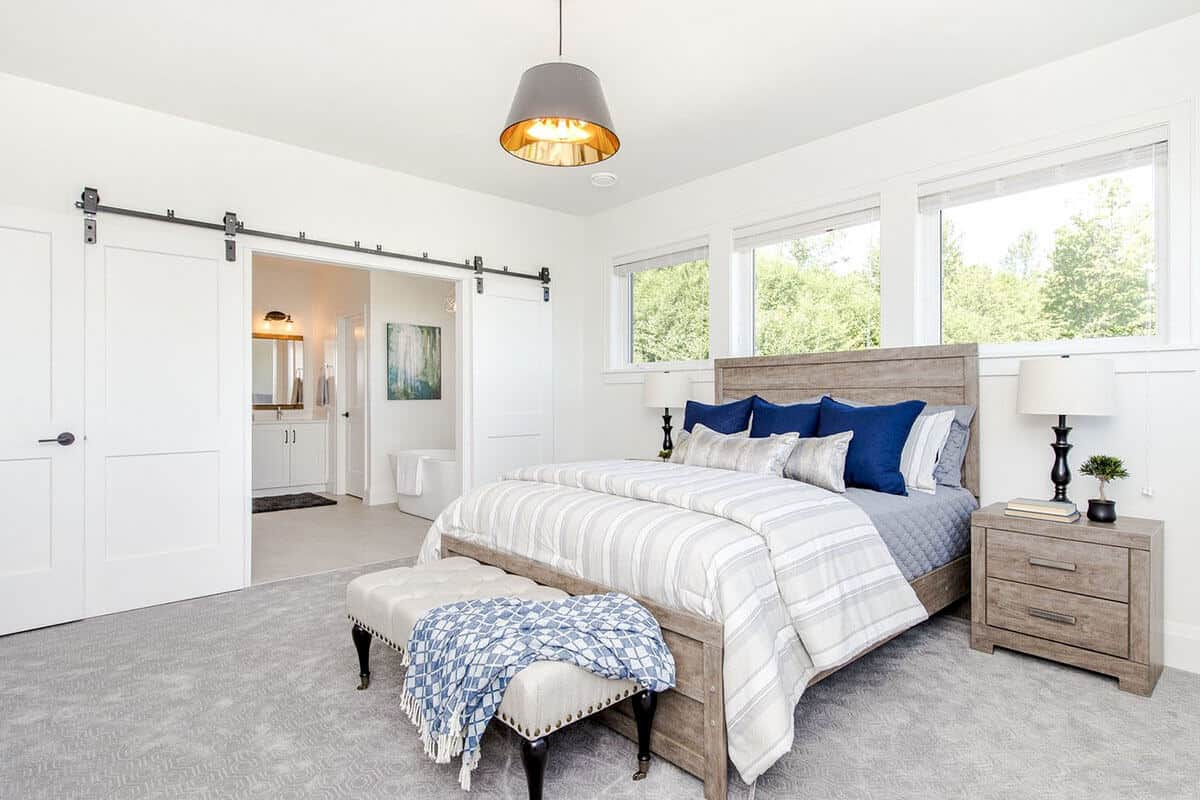 The light gray carpeted flooring of this Farmhouse-style bedroom is a perfect complement to the wooden sleigh bed with a wooden headboard and its matching bedside drawers with the same wooden hue that complements the white walls.