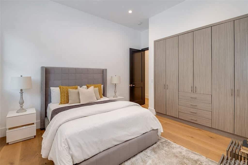The wooden cabinets and drawers are embedded into the white wall beside the light gray bed with white sheets. The light gray cushioned headboard is flanked by a couple of table lamps on white bedside drawers that stand out against the hardwood flooring.