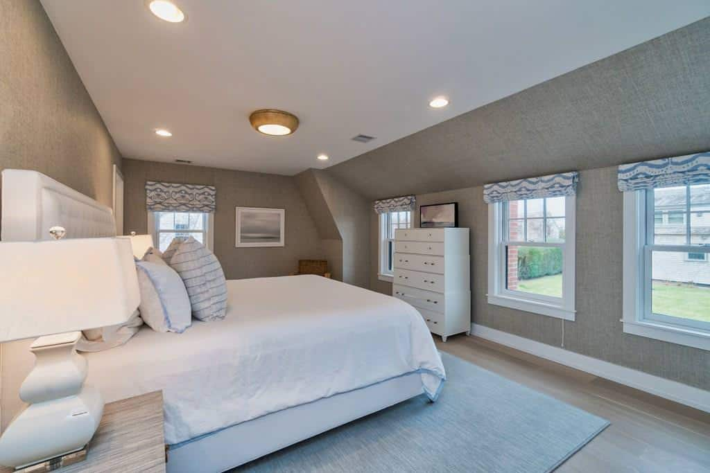 This is a cozy Farmhouse-style bedroom with a bright white bed and ceiling that shines due to the abundance of natural lights coming from the row of windows. This is counterbalanced by the gray walls and hardwood flooring topped with an area rug.