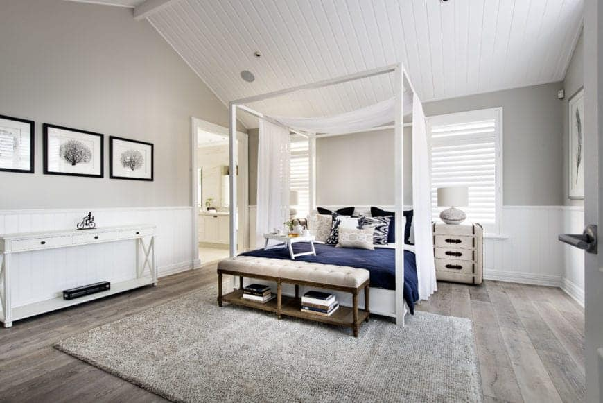 The white wooden four-poster bed pairs well with the white wainscoting and the white wooden finish of the cathedral ceiling that is complemented by the light gray walls and the bright natural lights coming in from the shuttered windows.