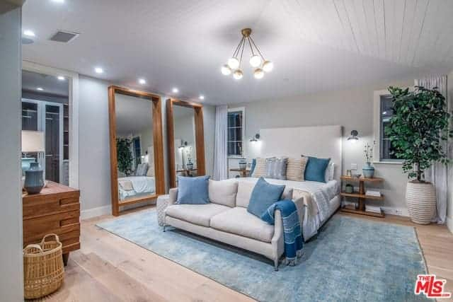 There is a pair of large wood-framed mirrors leaning on the light gray wall beside the bed that has a large cushioned headboard flanked by wall-mounted lamps over wooden bedside tables with a unique design blending with the hardwood flooring that is topped with a light green area rug.