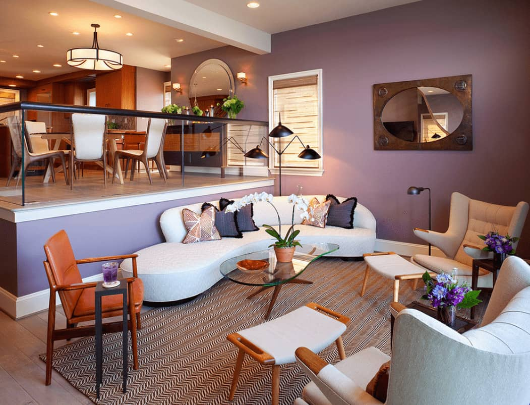 An open living area with a sleek sofa and modern armchairs surrounding a glass top coffee table that sits on a striking rug. It has wide plank flooring and lilac walls accented with a framed mirror.