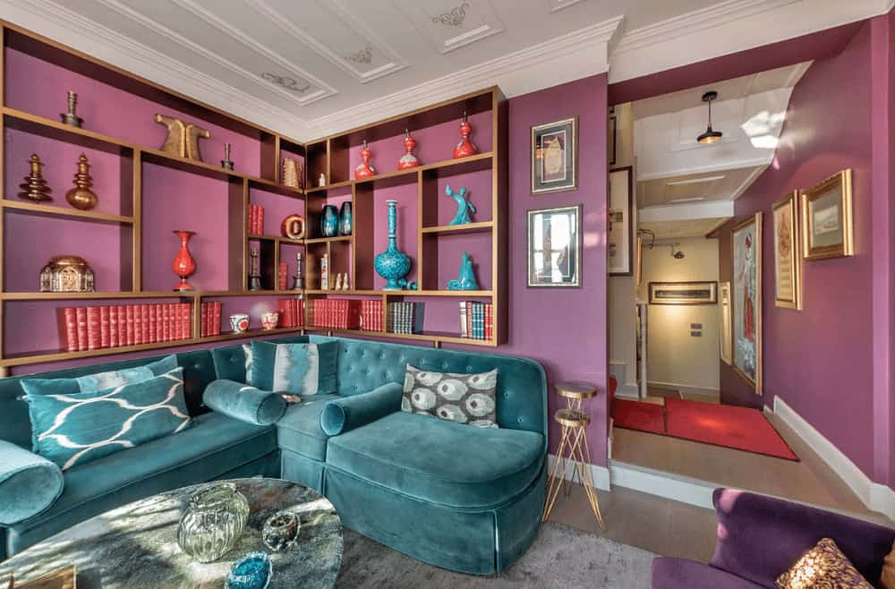 Eclectic living room boasts built-in shelving and a blue velvet sofa paired with a coffee table that's topped with glass bowls. It has a stylish ceiling and purple walls lined with white crown molding.