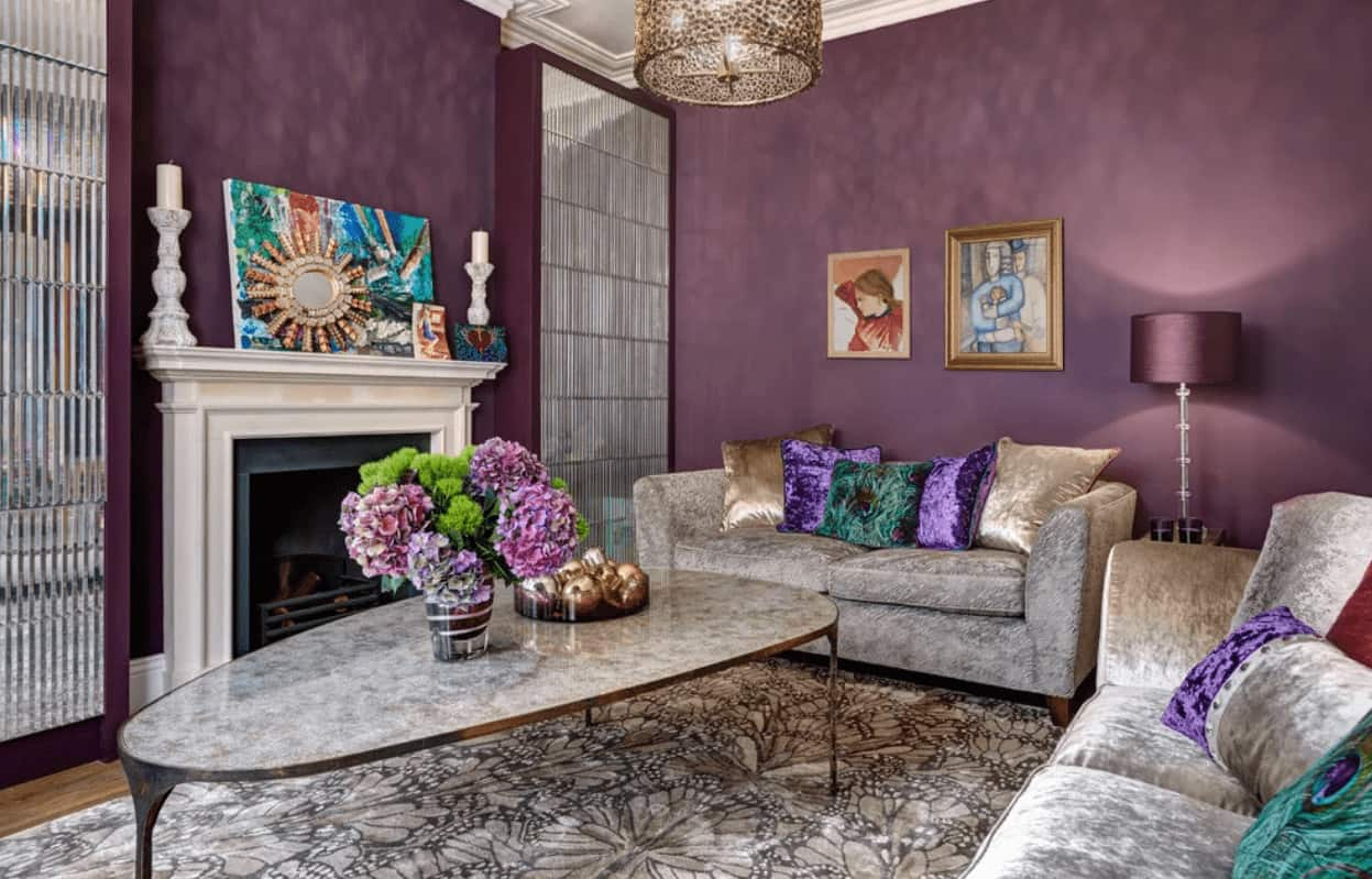 Fabulous living room illuminated by a glass floor lamp and stylish drum pendant that hung over the coffee table complementing with the velvet sofas that are accented with multi-colored pillows.