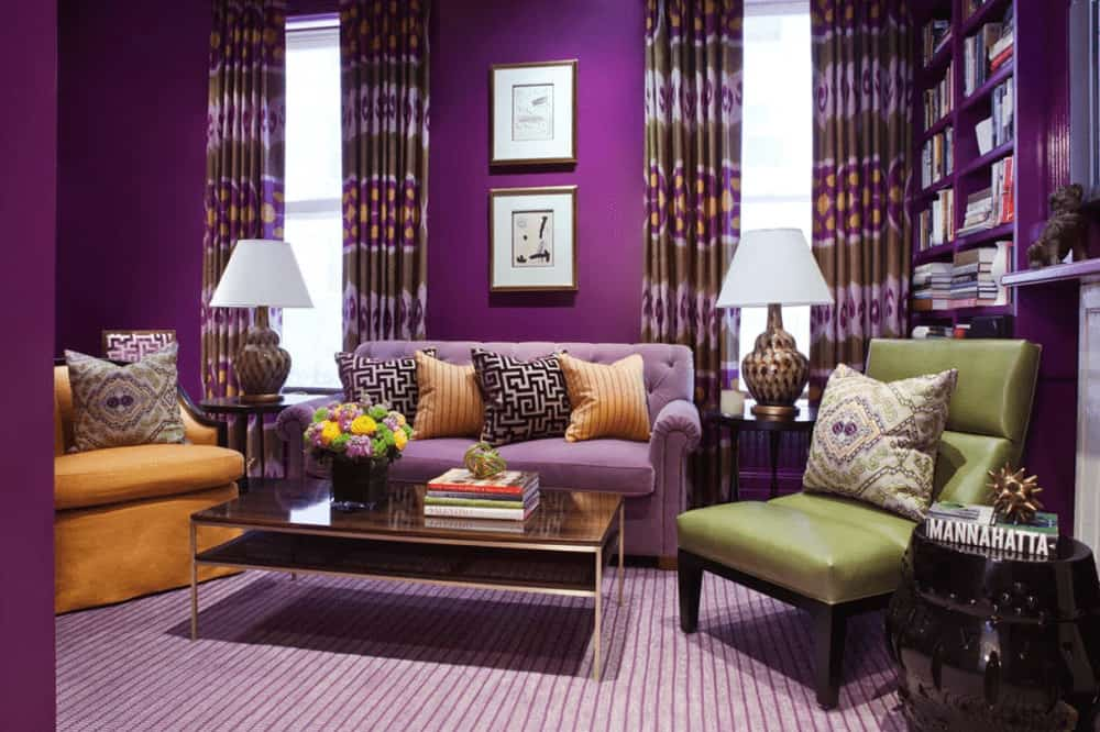Purple living room boasts mismatched chairs and printed draperies covering the glazed windows. It includes various styled pillows and a metal coffee table that sits on a striped area rug.