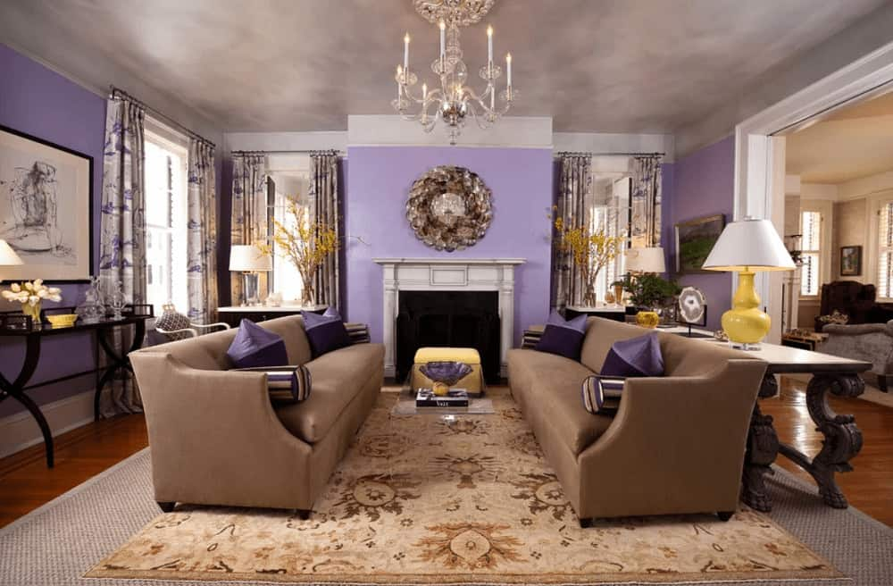 A glass coffee table sits in between brown sofas accented with purple pillows. This room has a candle chandelier and a white fireplace fixed on the lilac wall.