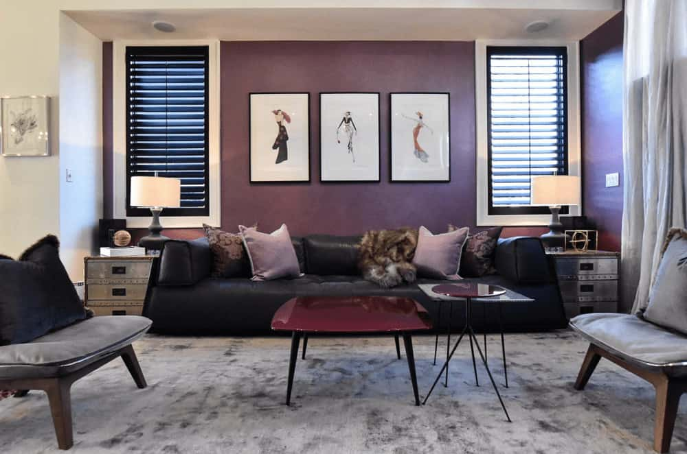 Wooden side tables and drum lamps flank a black leather sofa paired with a modular coffee table. This room showcases black framed wall arts and cushioned chairs that sit on a gray area rug.