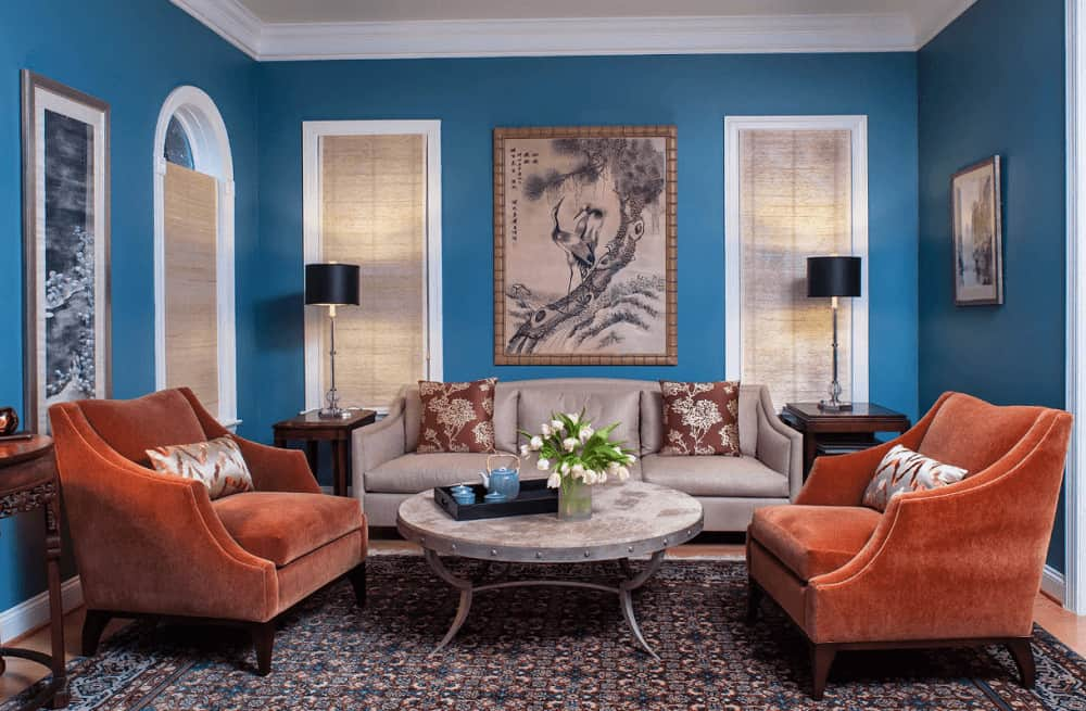 Traditional living room decorated with lovely artworks mounted on the blue walls. It has orange velvet chairs and a taupe sectional paired with a round coffee table that sits on a patterned rug.