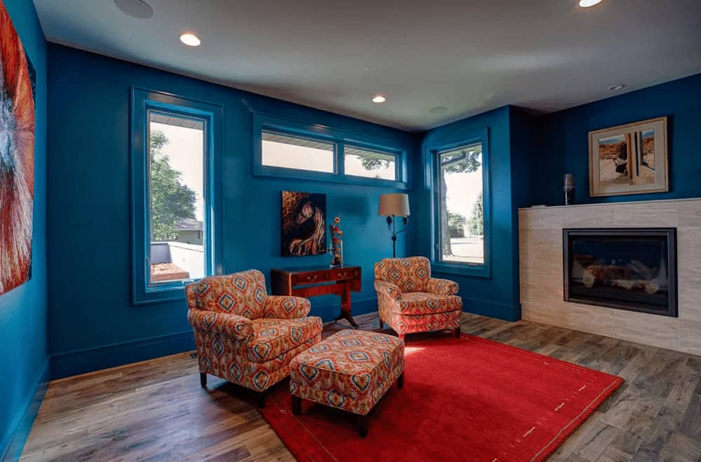This living room showcases a fireplace and patterned armchairs paired with a matching ottoman over a red area rug. It has natural hardwood flooring and blue walls mounted with artworks.