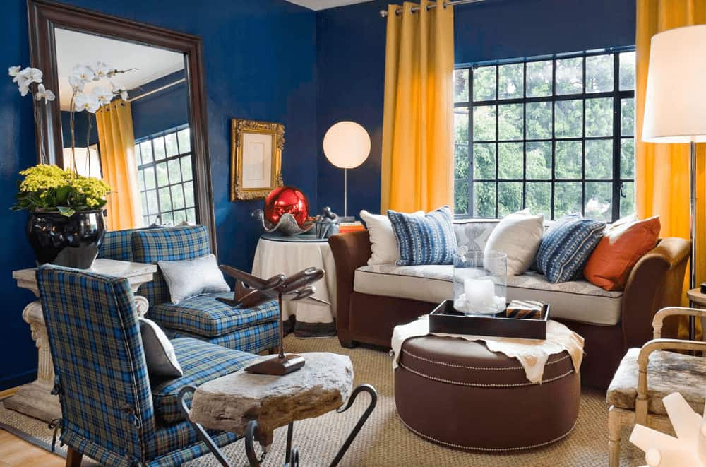 Yellow draperies covering the aluminum-framed window stand out in this blue living room with a large mirror and mismatched seats surrounding a round ottoman that sits on a jute area rug.