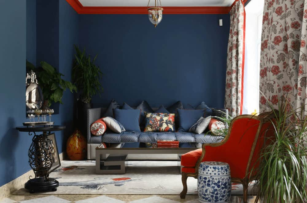 Red crown molding provides a sleek contrast to the blue walls within this living room. It complements the wingback chair accompanied by a cushioned sofa and sleek coffee table.