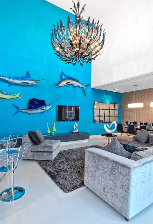 An open living area designed with fish wall decors and a stunning chandelier that hung over the gray shaggy rug. It has velvet seats and a flat-screen TV hanging above the sleek console topped with contemporary sculptures.
