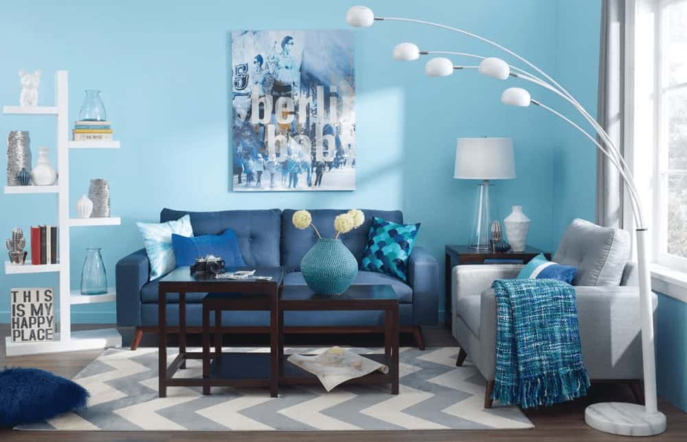 A white shelving unit complements the arched five head floor lamp illuminating the tufted seats and modular coffee table that sits on a gray chevron rug. This room is decorated with lovely artwork mounted on the sky blue wall.