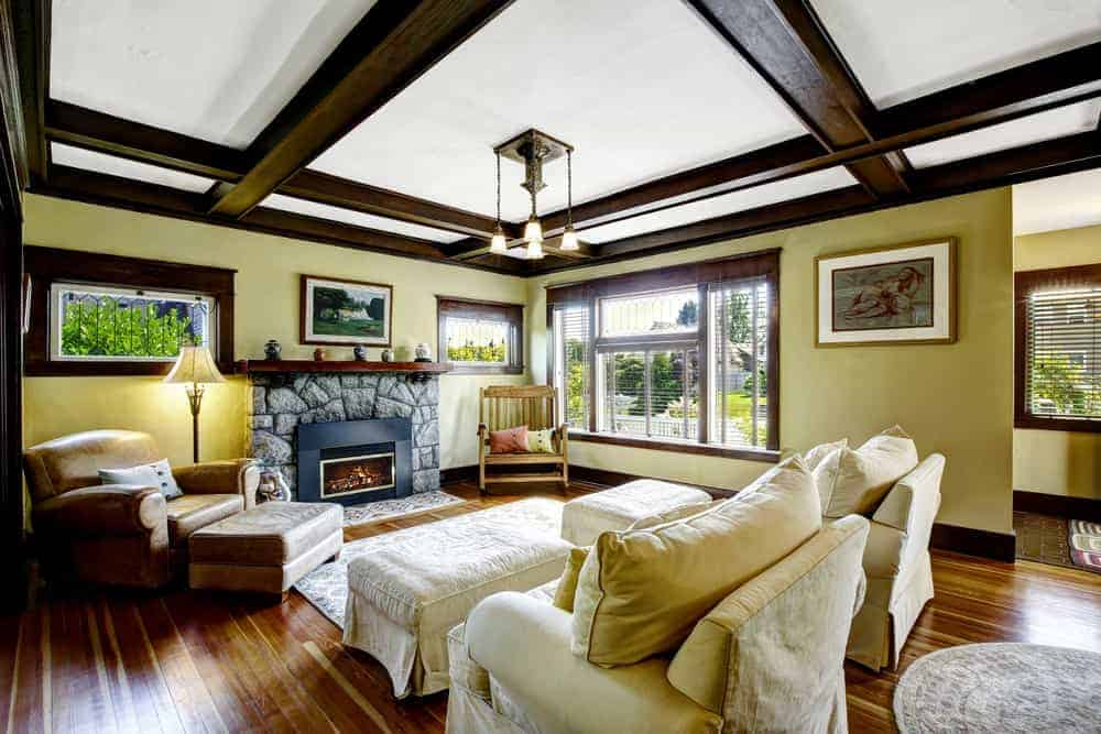 A spacious Country-style formal living room offering a set of classy seats and a stone fireplace under the home's elegantly-designed ceiling.