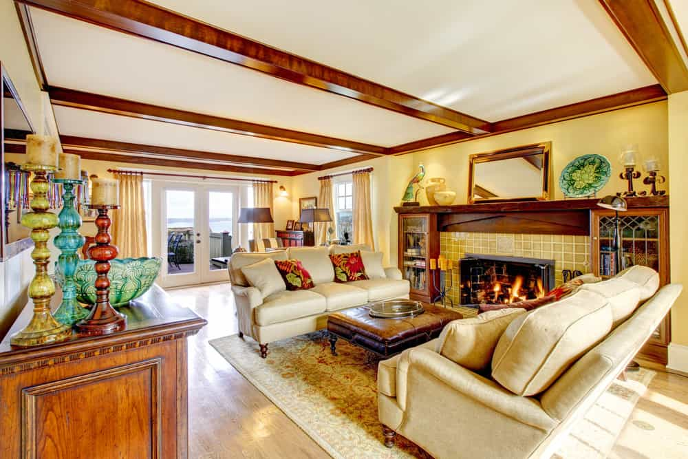 A spacious Country-style living room with a set of nice couches set on a classy area rug covering the hardwood flooring. The elegant fireplace keeps the place warm.